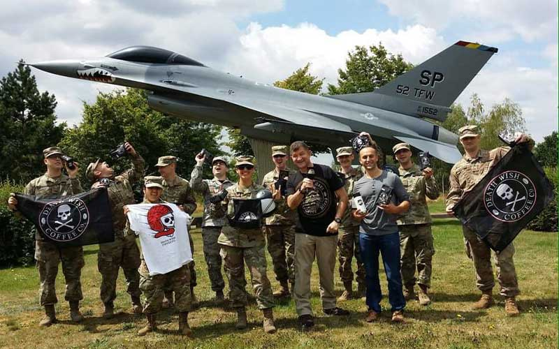 U.S. soliders in front of a Air Force jet holding a Death Wish Coffee flag
