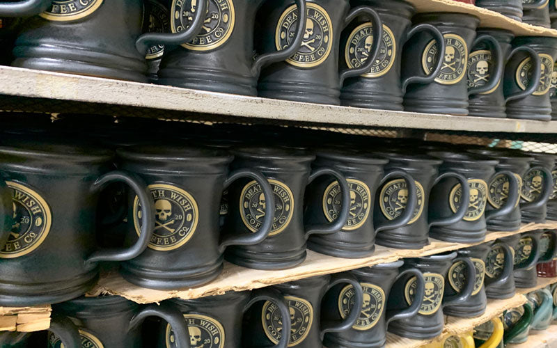 A photo of three shelves lined with 2020 Death Wish Coffee mugs in a matte black glaze