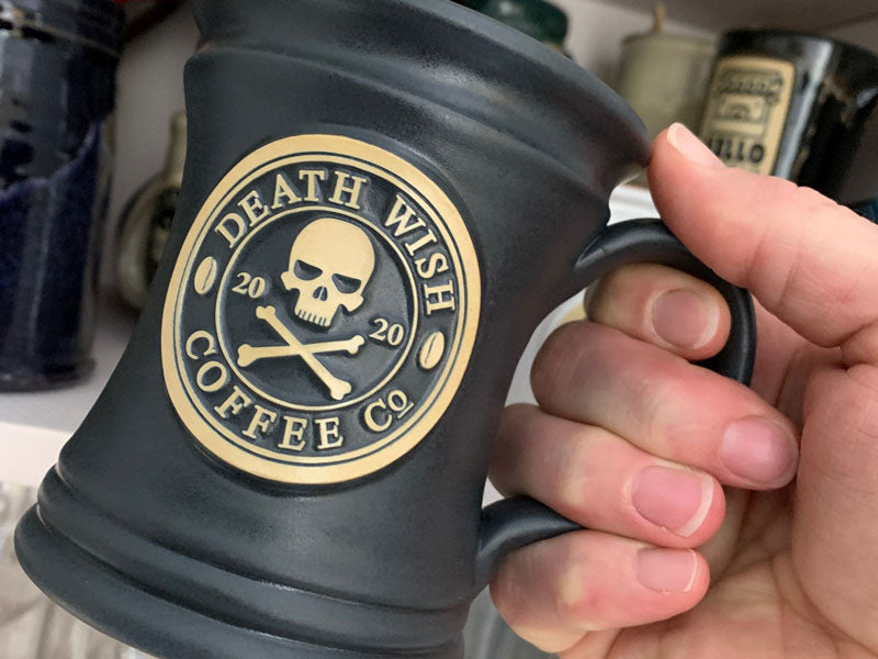 A close-up of a person holding a Death Wish 2020 ceramic mug, which is in a black glaze and includes a skull and crossbones logo