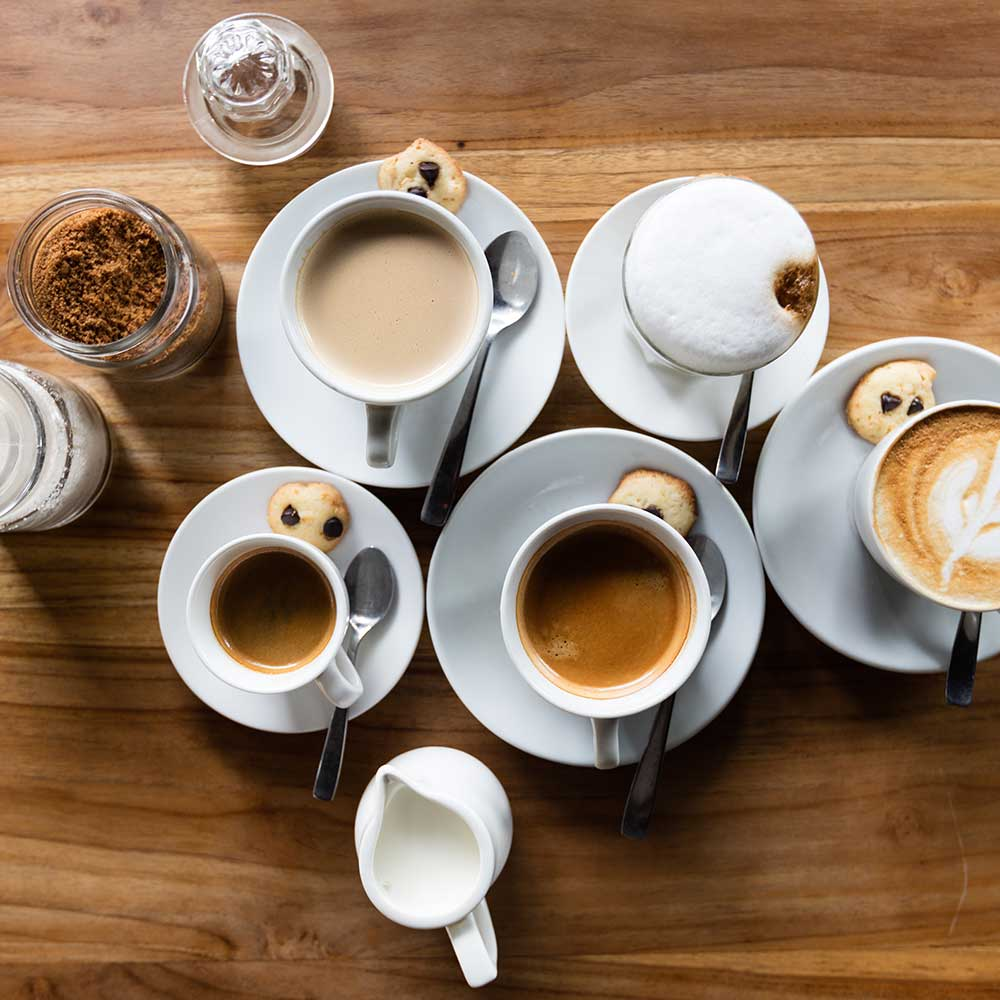 Various cups of coffee on a wooden table.