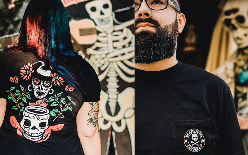 A man and a woman wearing Death Wish Coffee Halloween-themed shirts