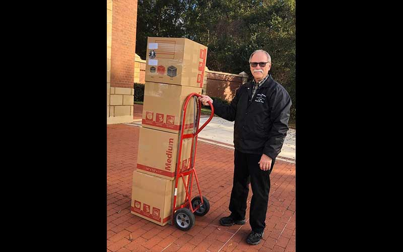 Brian Dunmyer transporting boxes using a hand truck