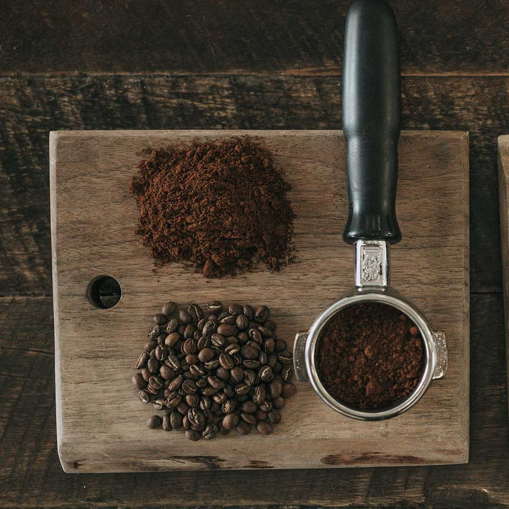 An image of a coffee grinder on a table with whole bean and coffee grounds.