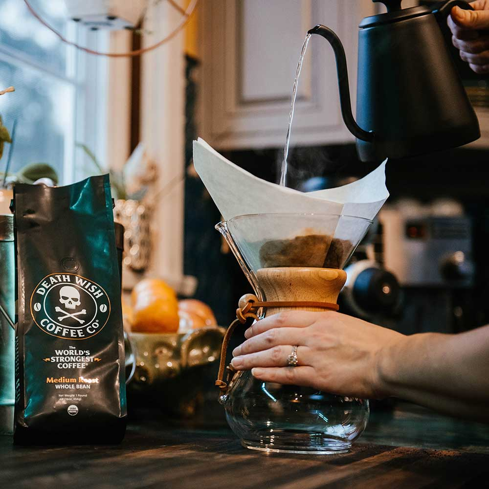 An image of water being poured into a Chemex with a bag of Medium Roast coffee in the background.