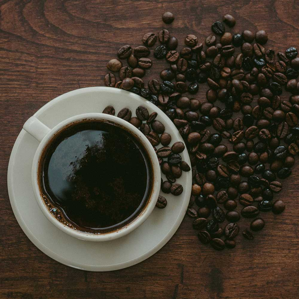 An image of a coffee mug filled with black coffee and coffee beans spilling on the table.