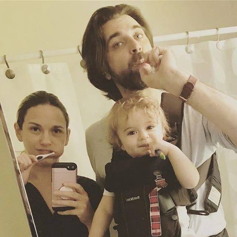 Dave and Jes Hudak brushing their teeth while holding their daughter