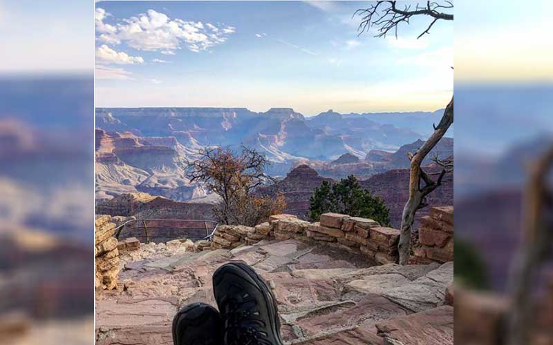 Grand Canyon vista with someone's black shoes resting in the foreground