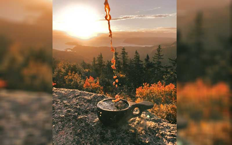 Coffee being poured into a cast iron cup in front of a Cape Breton Island, Nova Scotia vista