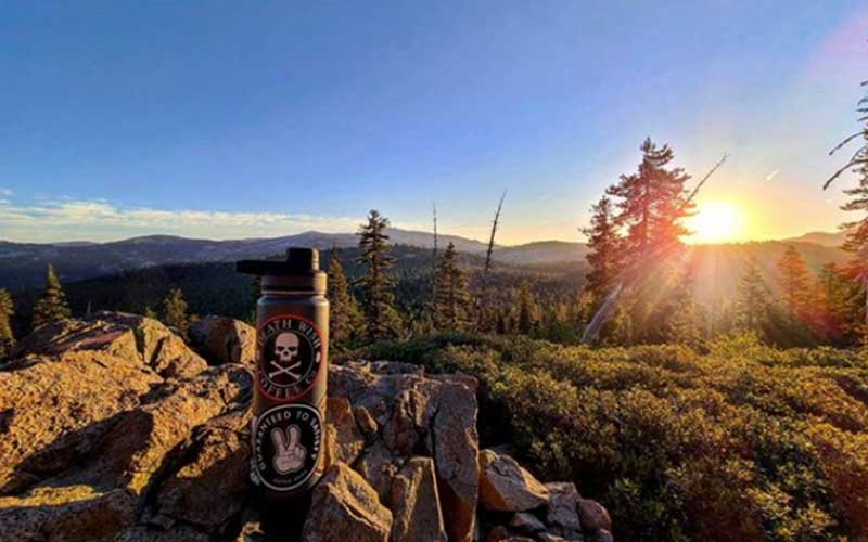 Water bottle decorated with Death Wish stickers in front of expanse in Soda Springs, California