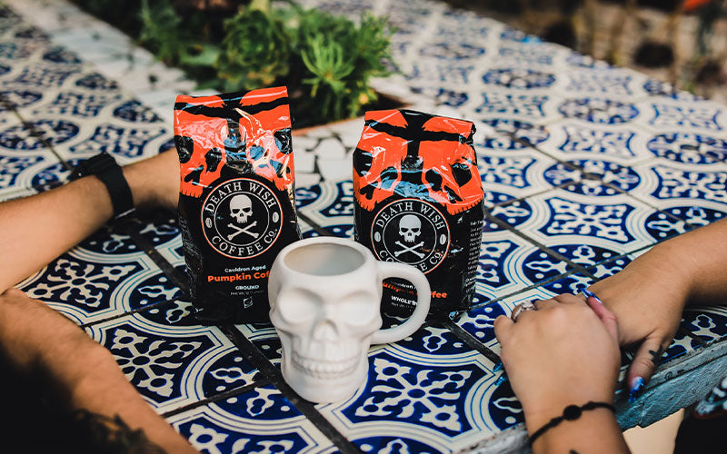 Two people talking at a table over a skull mug and two bags of Death Wish Cauldron-aged pumpkin spice coffee