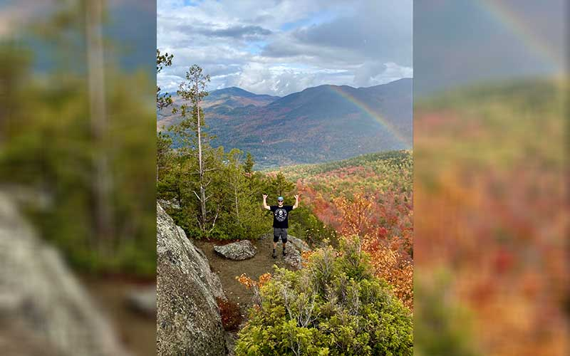 Man below a rainbow, surrounded by a autumnal forest in Adirondacks, New York