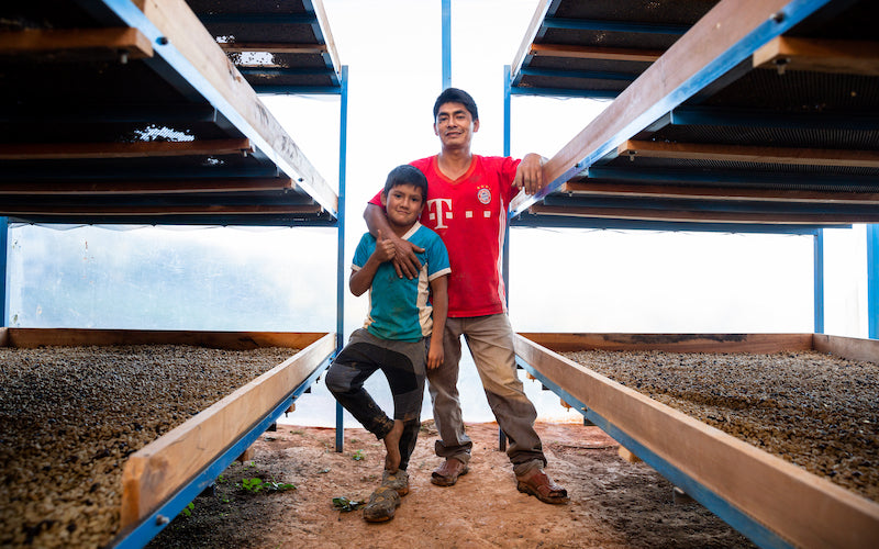 A father and son pose for a photo in a coffee bean drying room.
