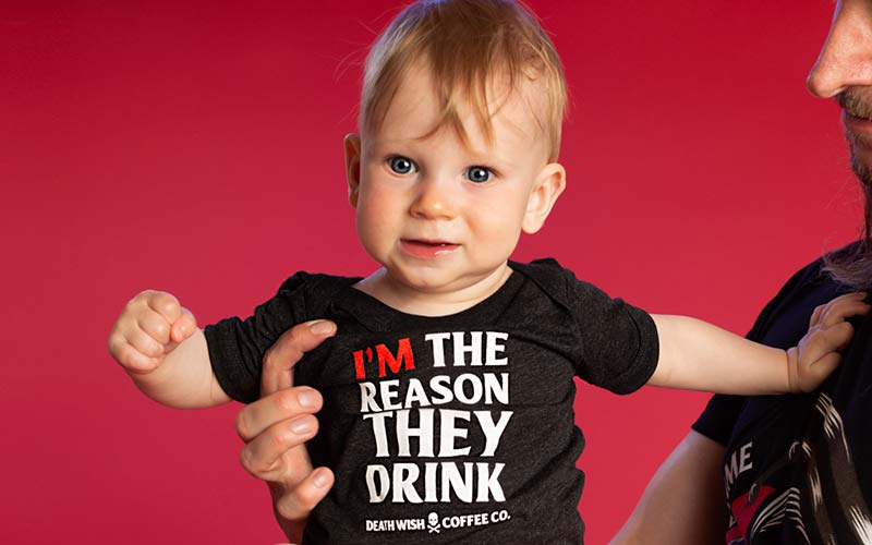 """A baby wearing a onesie that says """"I'm the reason they drink."""""""