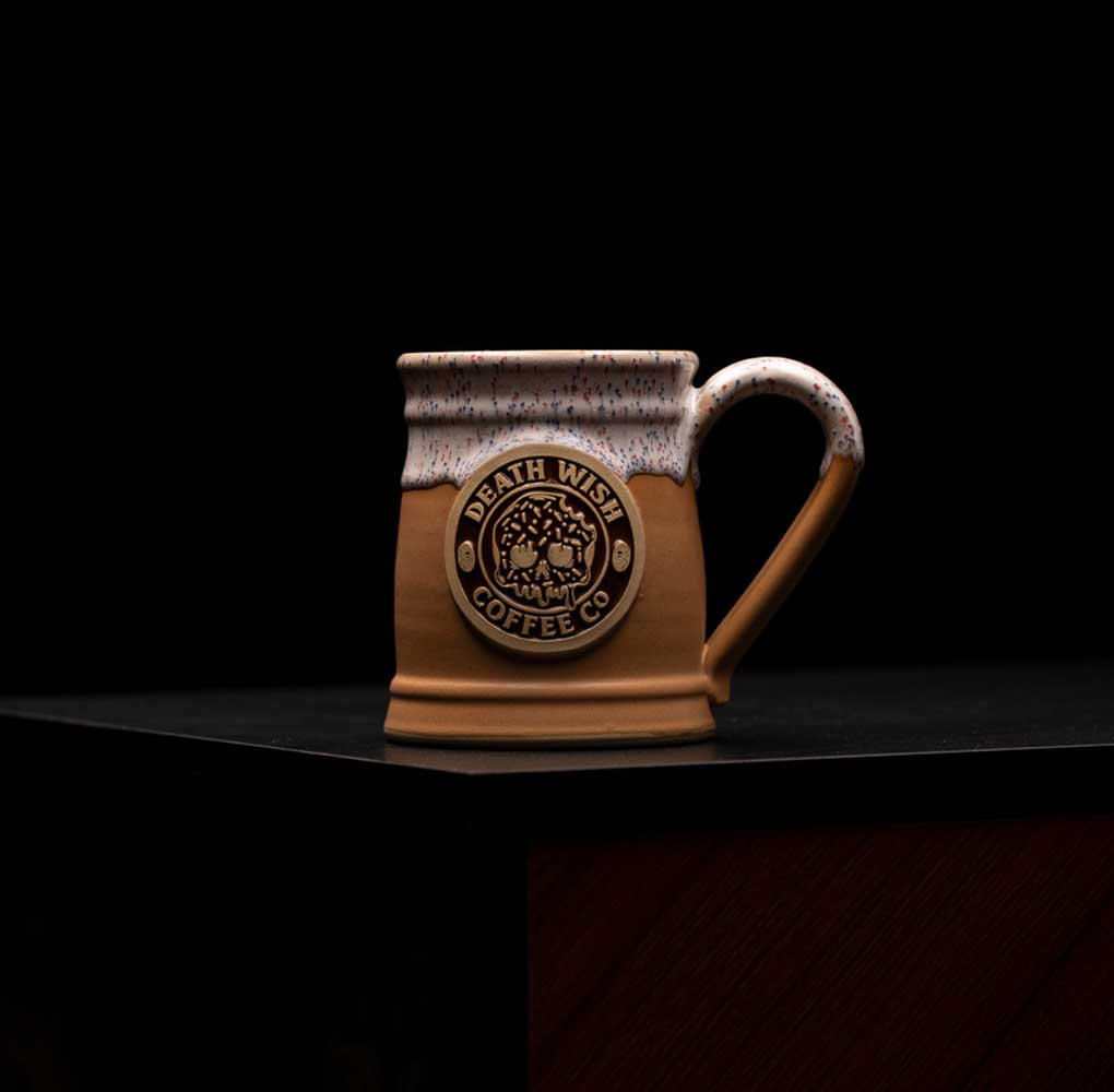A brown and white donut mug featuring a donut themed mug medallion on a black background.