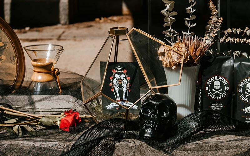 A wedding save the date card with two skeletons on it sitting in the centerpiece of a table decoration.