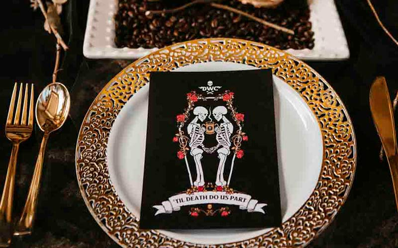 Table setting for a wedding featuring a skeleton save the date card on a white and gold plate.