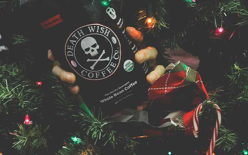 Hand holding a bag of Death Wish Coffee in front of Christmas tree branches