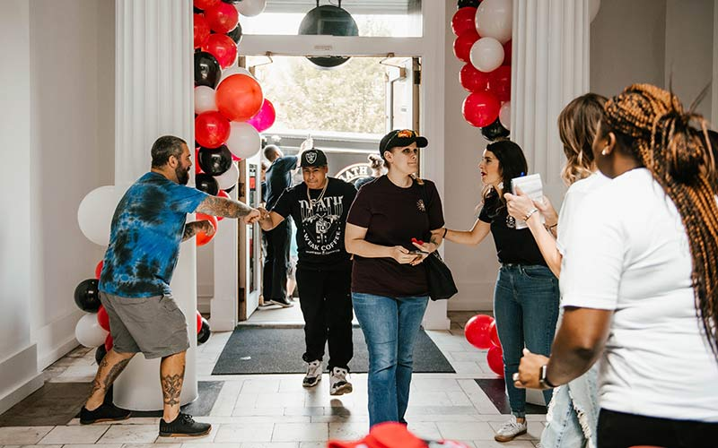 The first customers to enter the grand opening of the Death Wish Coffee retail shop being greeted by the Death Wish Coffee employees.