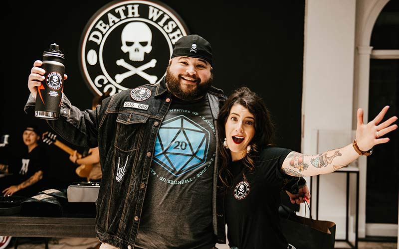 A Death Wish Coffee customer and Death Wish Coffee lifestyle director posing in front of the skull and crossbones logo.