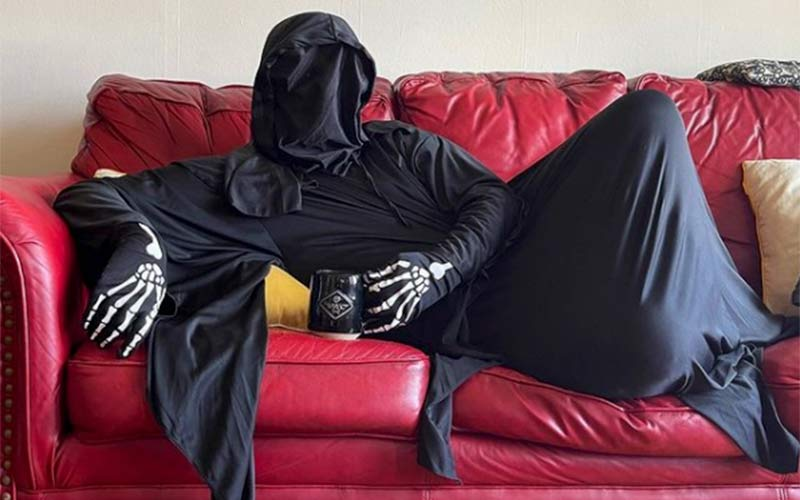 A person in a Grim Reaper costume sitting on a red leather couch with a mug of Death Wish Coffee.
