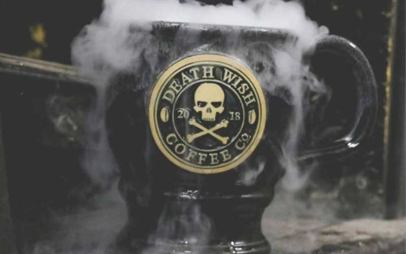 A black Death Wish Coffee mug with smoke coming out the top.