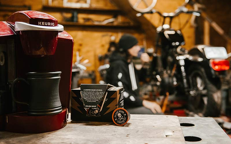 A red Keurig coffee maker with a box of medium roast death cups and in the background a mechanic working on a motorcycle.