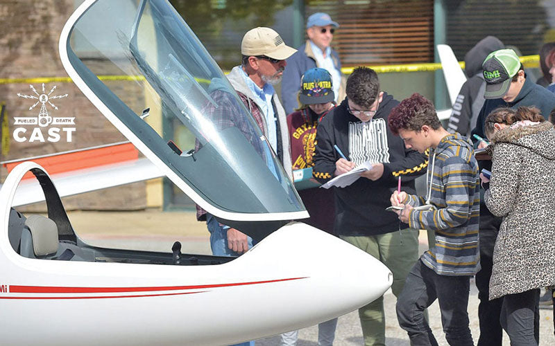 Middle School Students stand around an airplane glider with an instructor