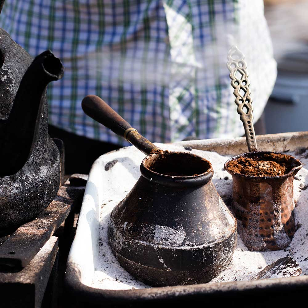 An image of Turkish Sand Coffee being brewed over a stovetop.