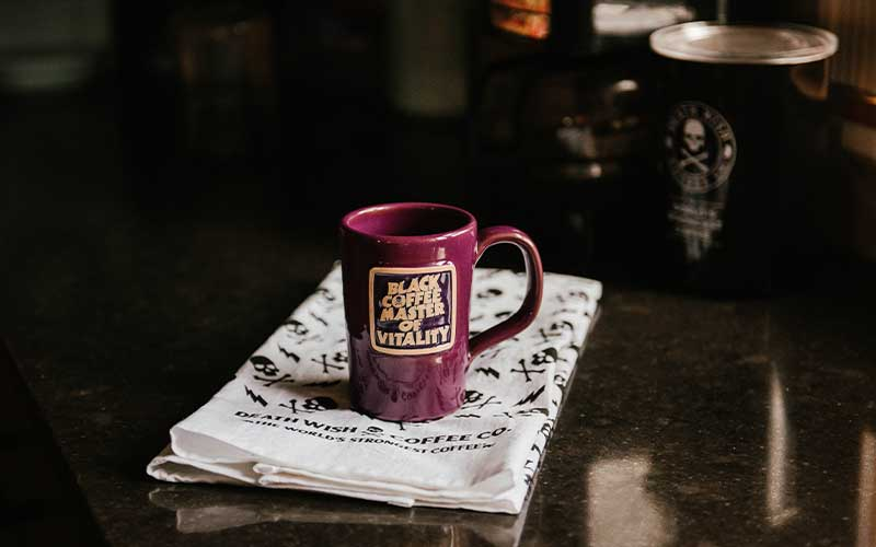 """Mug that reads """"Black Coffee Master of Vitality"""" sitting on top of a Death Wish Coffee towel"""