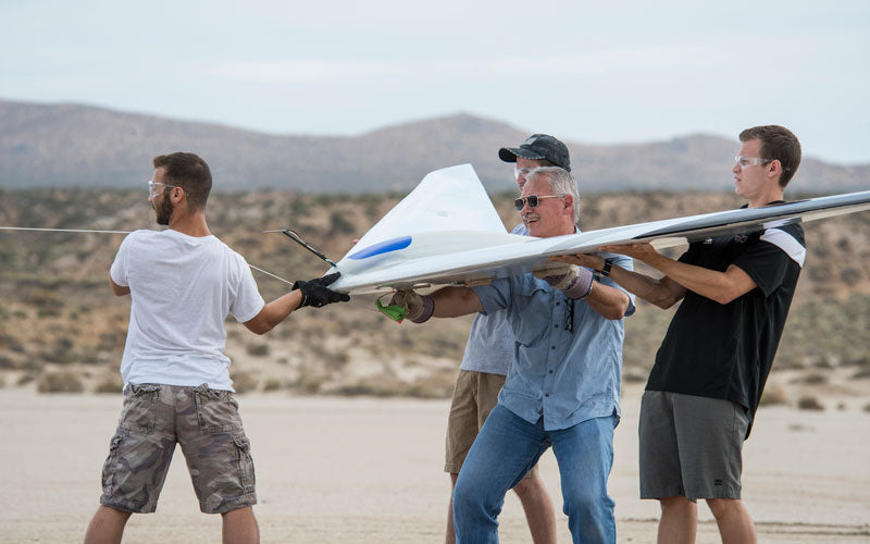 Al Bowers, center, and a group of student interns hook up a bungee cord for a flight of the Prandtl-D 3C subscale glider aircraft, which all four of them are holding