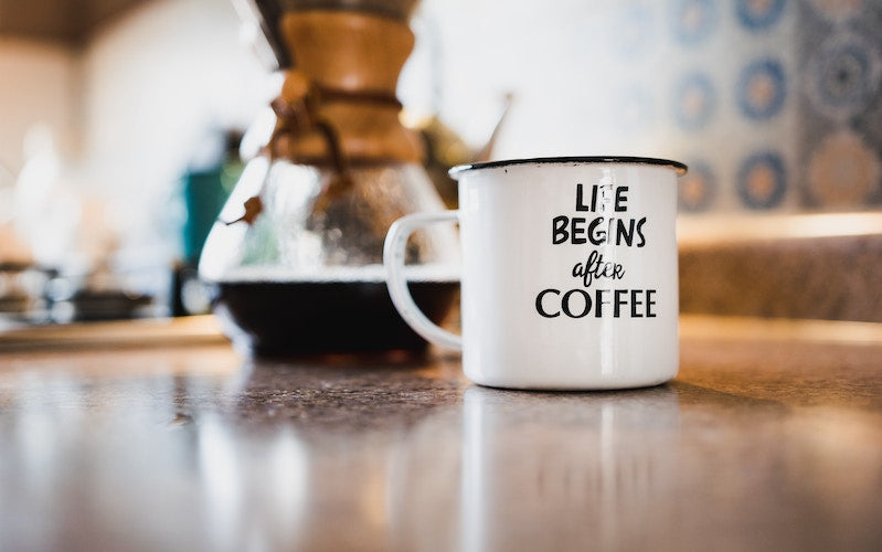 "A white mug of coffee that says ""Life Begins After Coffee"" sits on a kitchen table"