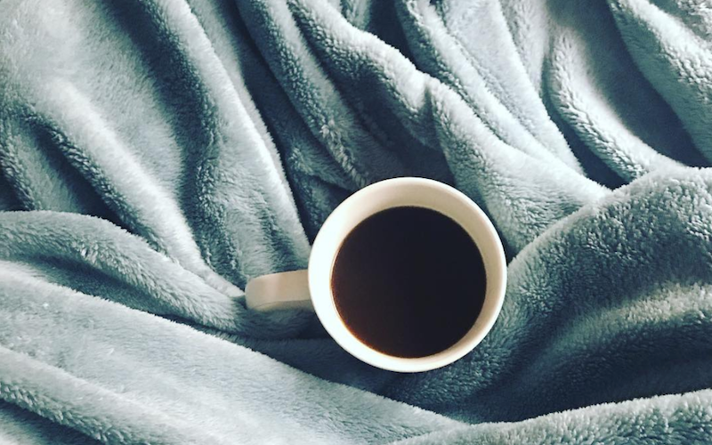 Cup of coffee surrounded by a blanket