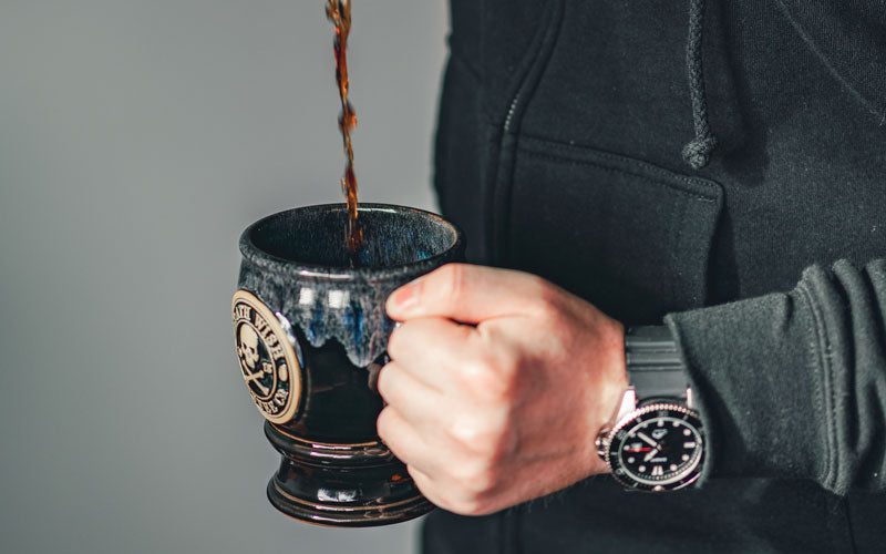 A male with a watch on holds a coffee cup while coffee is being poured into it