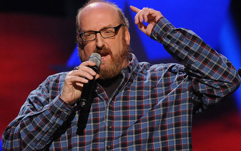Comedian Brian Posehn is shown on stage doing stand-up comedy