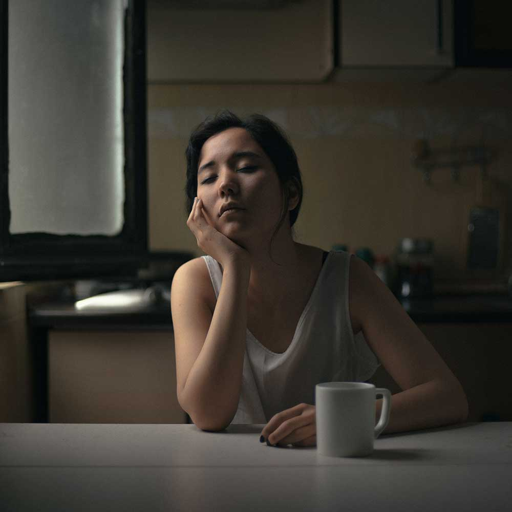 A woman falling asleep at the table with a mug of coffee in front of her.
