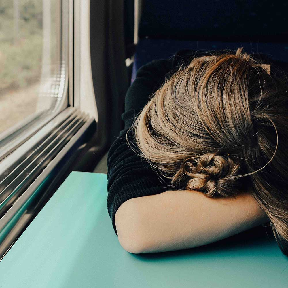 A young female on a train with her head in her arms on a table.