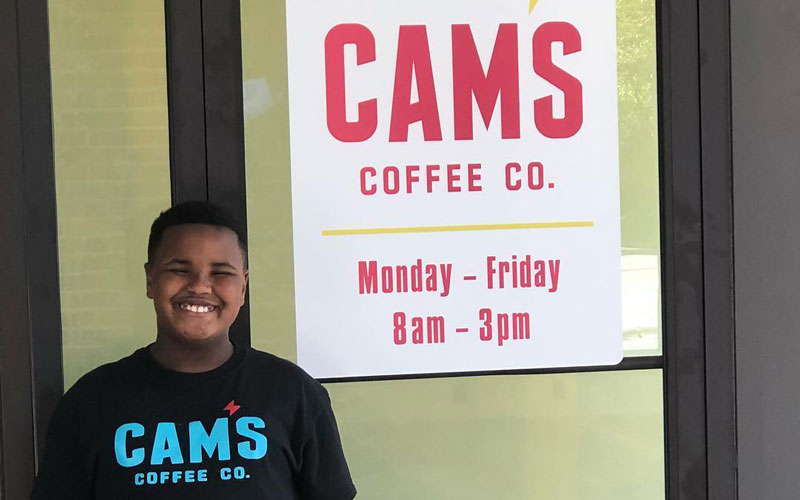 A photo of Camden Myers, the 9-year-old owner of Cam's Coffee Co., standing in front of a red store sigh
