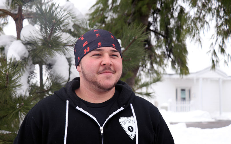 A male wearing a red and black bandana as a hat that's tucked in at the base of his skull
