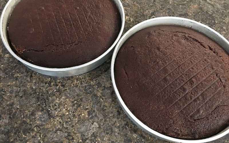 Two pans filled with chocolate cake, fresh out of the oven.