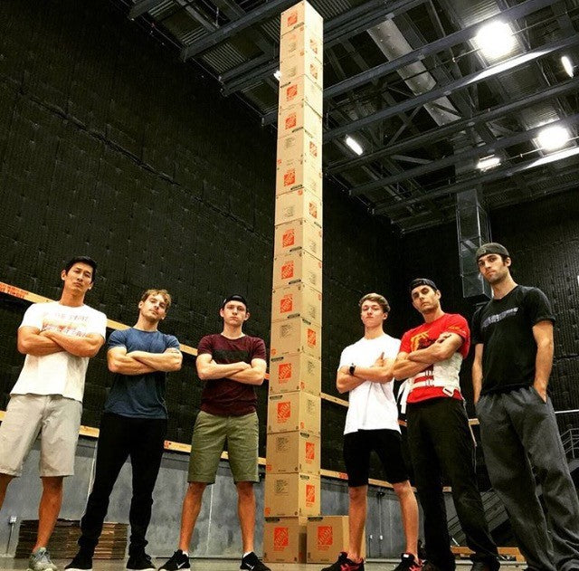 Group of men standing next to a stack of boxes