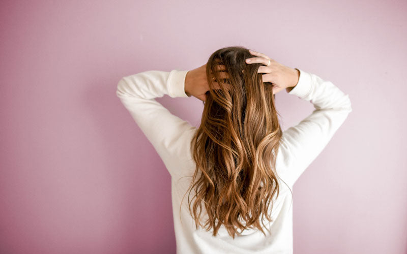 The back of a girl's head showing her running her hands through long wavy brown hair and standing in front of a pink wall