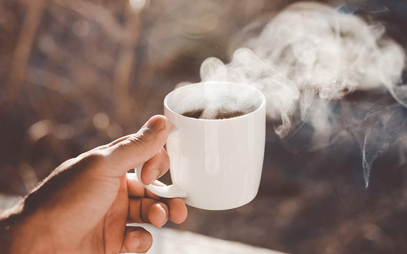 A cup of steamy hot coffee being held in the air outside.