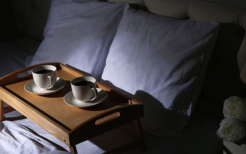 Two cups of coffee sitting on a tray on a bed with two blue pillows