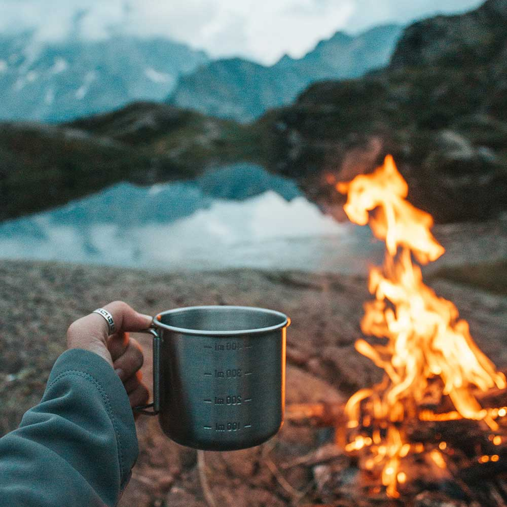 A mug of coffee being held up next to a campfire overlooking a beautiful lake surrounded by mountains.