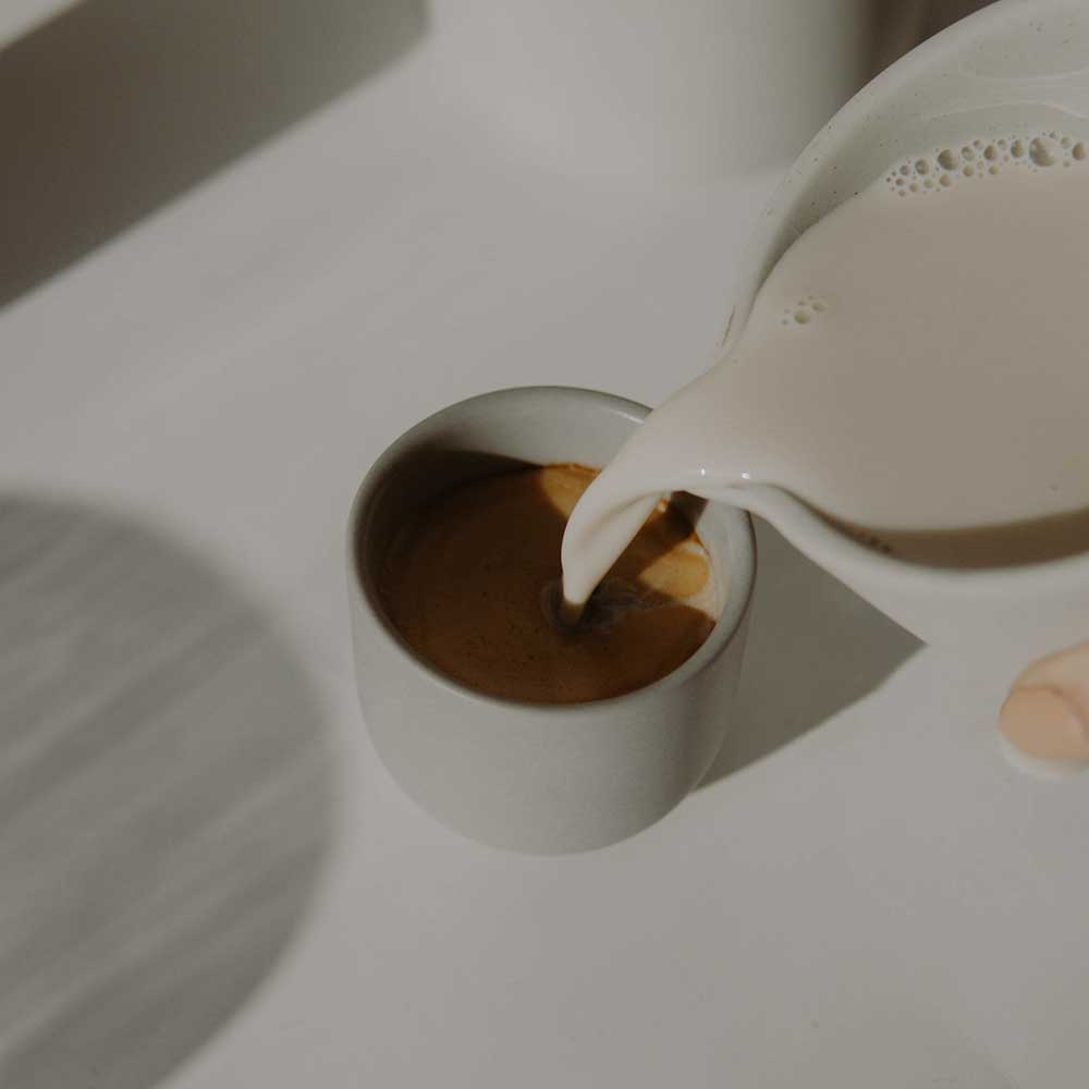 An image of creamer being poured into a coffee mug