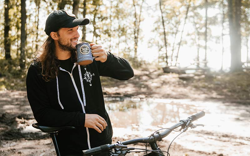 A man on a mountain bike in the woods smiling as he sips a mug of coffee.