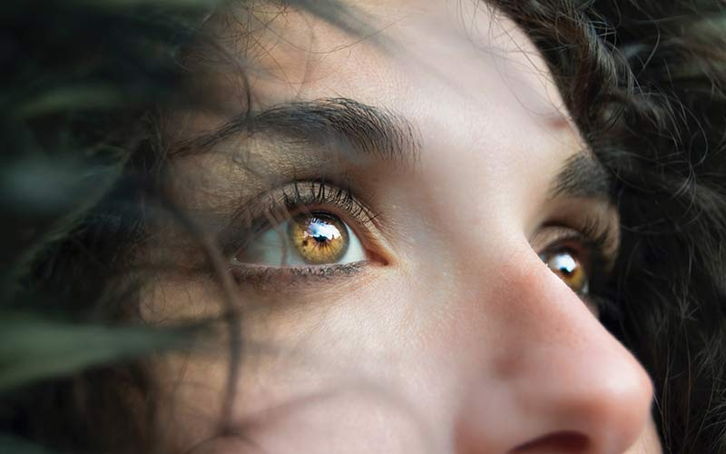A close-up of a woman's eyes. The eyes are light golden brown.