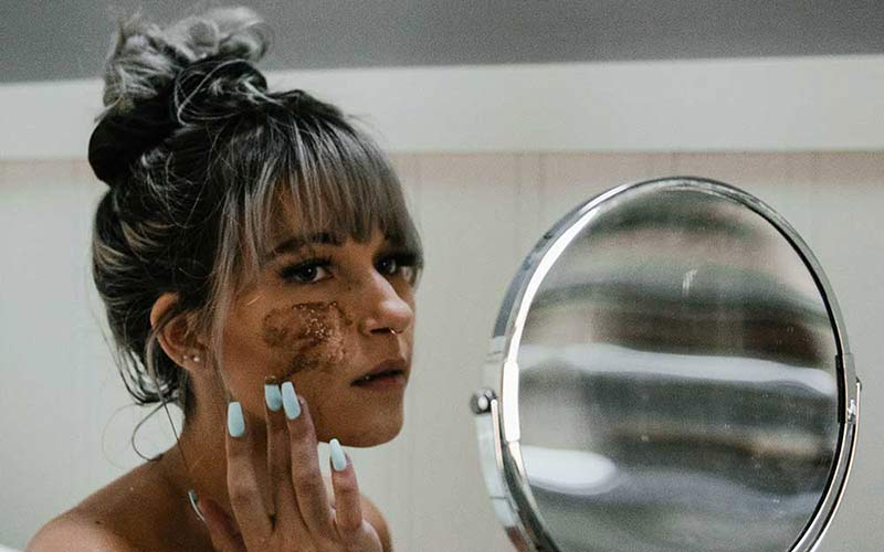 A woman applying a coffee face mask with coffee grounds.