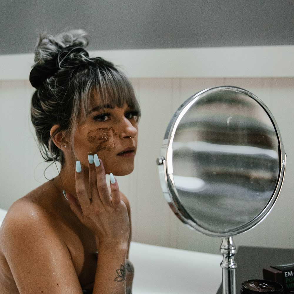 An image of a female applying a coffee face mask in the bathroom.