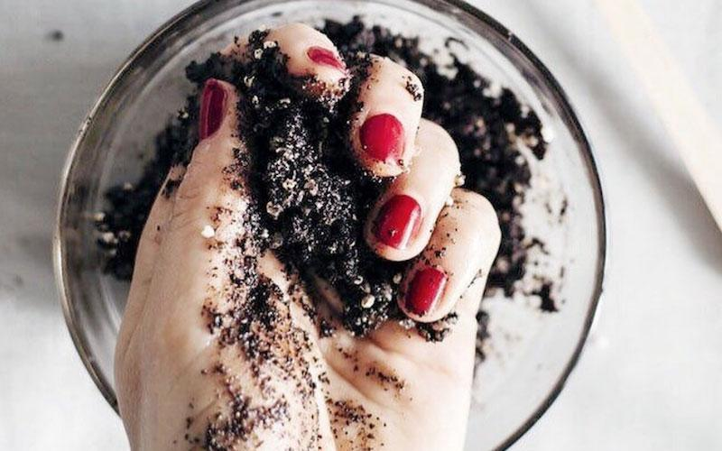 A woman with painted red finger nails mixes a coffee face mask in a bowl with her hand